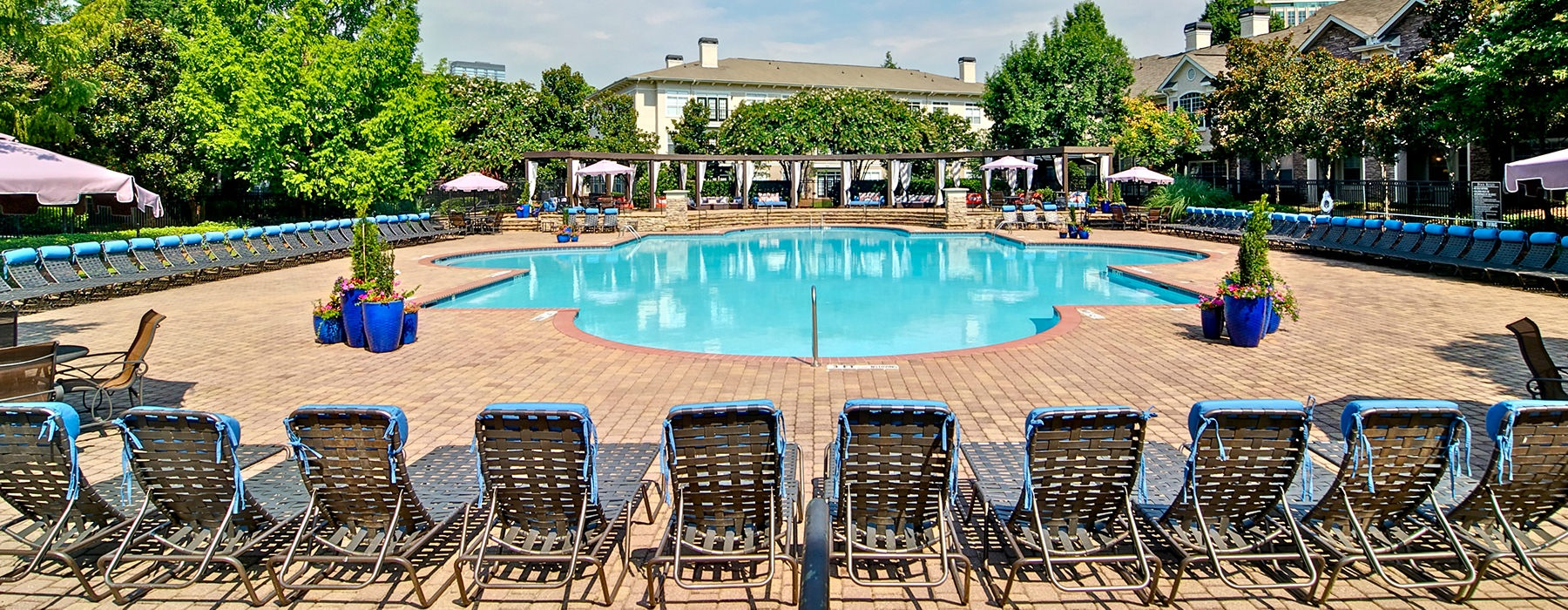 Large pool with resort-style chaise loungers at Aspire Lenox Park Apartments near Ridgedale Park